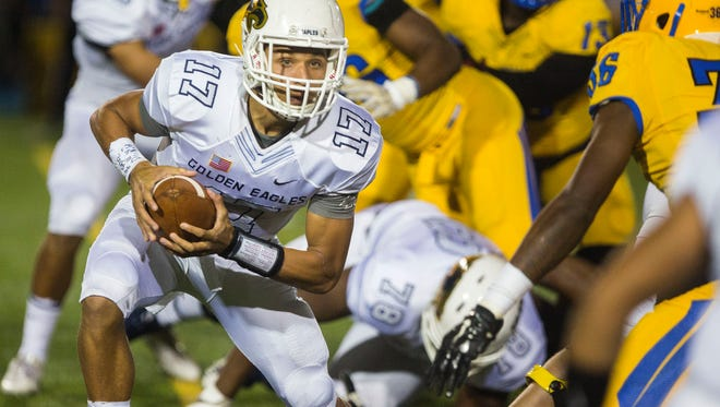 Naples quarterback Jordan Persad-Tirone looks for an opening to pass as Northwestern's defense closes in at the Nathaniel Traz-Powell stadium in Miami, where the Naples Golden Eagles took on the Northwestern Bulls on Friday, Dec. 1, 2017.