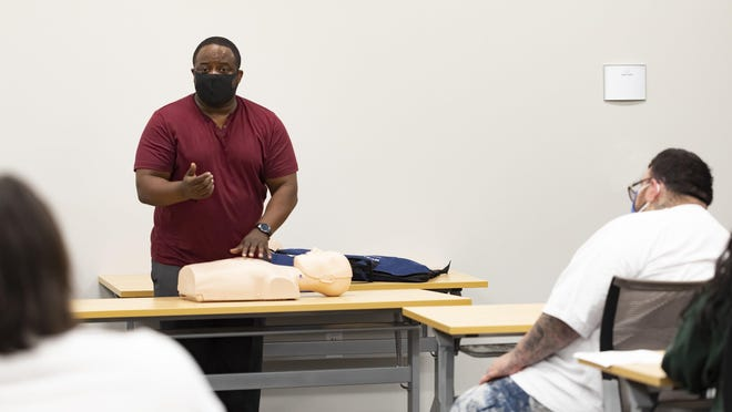 Todd Hamilton teaches a technique in class at Central Texas Allied Health Institute. The institute received a grant from St. David's Foundation to get more people of color trained in health fields.