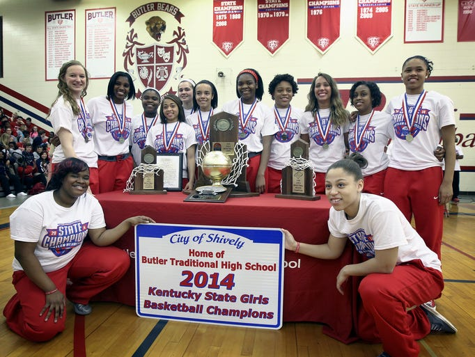 Members of the Butler Bearettes girls basketball team pose for photos with their state championship trophy and sign during a school assembly at Butler Traditional High School on Friday. March 21, 2014