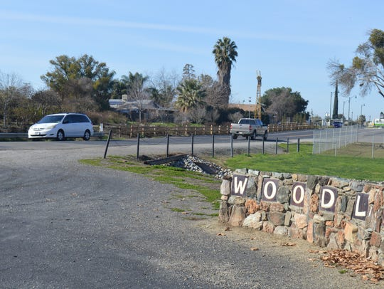 Two vehicles drive past the Woodlake sign Friday.