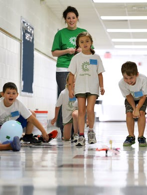 Seven-year-olds Emma Archambault (center) and Rowan Jenkins race the cars they built down a hallway during Camp Invention at Bessie Weller Elementary in Staunton on Friday, June 27, 2014.