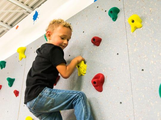 Hunter McCafferty makes his way up the rock wall at