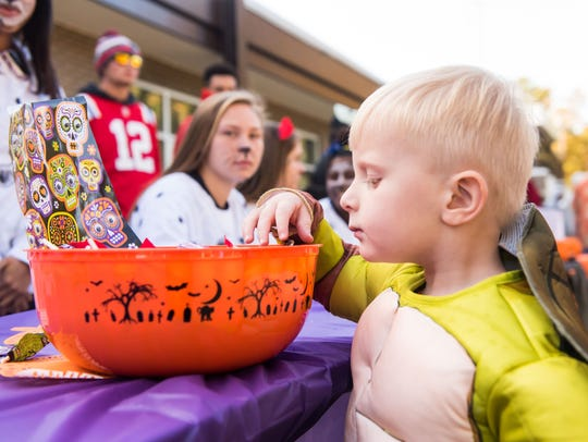 Braxton Ruiz, 3, sorts through a bowl of candy during