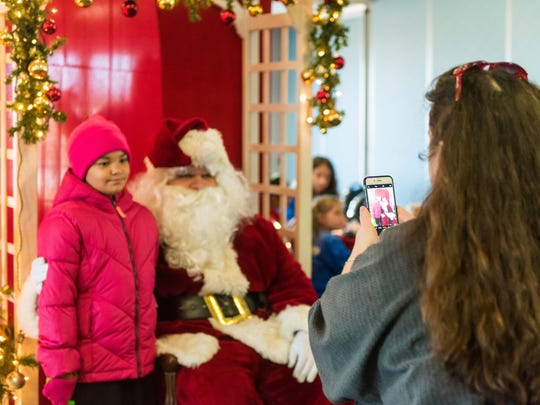 Nicole Lolley has her photo taken with Santa during
