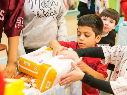 Bishop Schad students place various supplies for newborns
