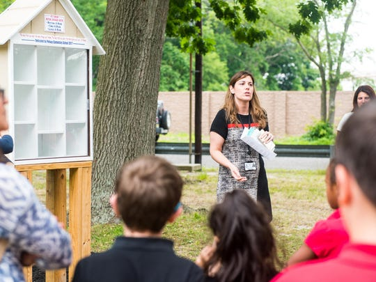 Petway Elementary Vice Principal Jaclyn Mongelluzzo speaks to students, staff and community members before filling the new book share box at Giampietro Park on Monday, June 5.