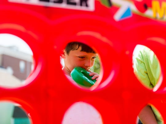 Jaden Dayton looks for a spot to place his marking while playing Connect Four during Millville's first Play Streets week on Pine Street in Millville on Wednesday.