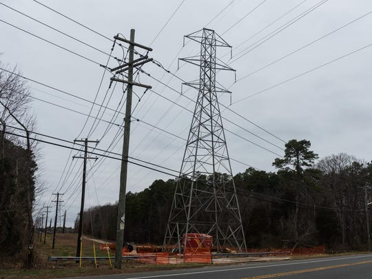 New steel poles lie on the ground near a lattice tower on North Delsea Drive where Atlantic City Electric is performing upgrades.