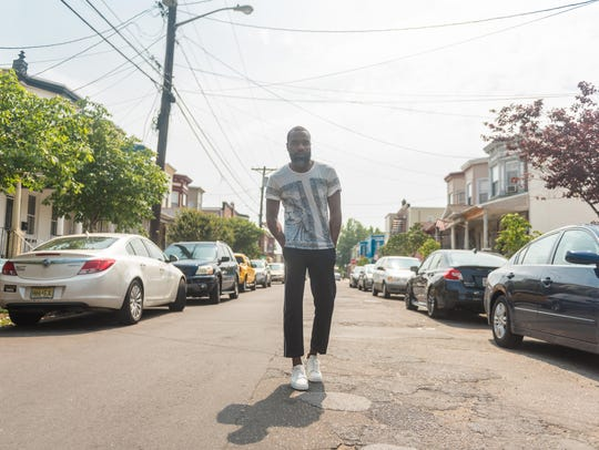 "Writer and activist Darnell Moore walks through a neighborhood in Camden. His book jacket quotes luminaries including author Dr. Cornel West, who called it ""a torturous yet triumphant journey through racist and homophobic America."""
