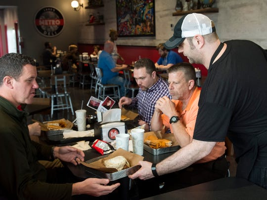 Owner/head chef Lake Russell serves up a sandwich to customers at Lake's Metro Deli on Tuesday, April 24, 2018.