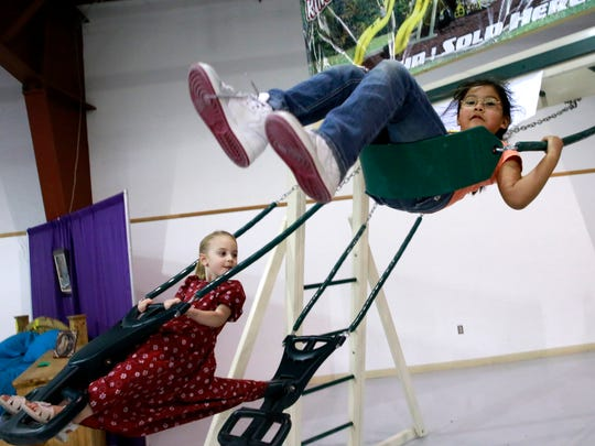 Abbie Martin, 6, front, and Alice Kuhns, 4, play on the swing set on display by The Barnyard during the San Juan County Home Builders Association Home Improvement & Building Expo on Saturday at McGee Park.