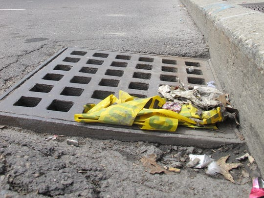 Debris piles up around a storm sewer Monday on Bank