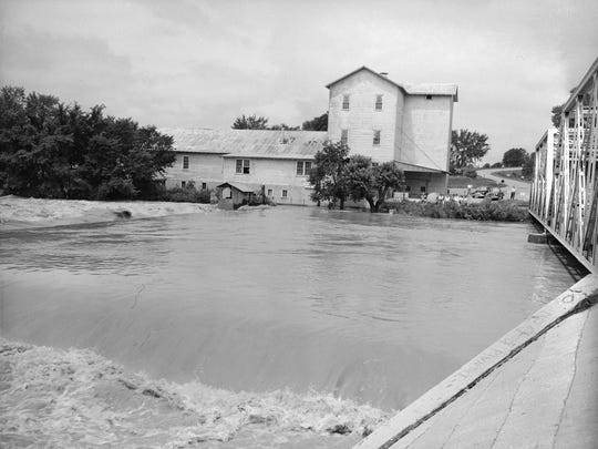 The Finley River flowing under the bridge in Ozark, Missouri. The river flooded over its banks and approached the mill house. This photo was originally published in July 1951.