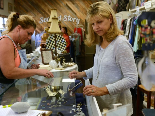 Shannon Spatz, left, gets a hand looking at items in