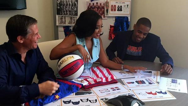 Cheese Chisholm (right) looks at designs by Angela Simmons (left) who designed a fashion line for the Globetrotters' 90th anniversary.