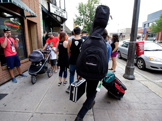 A musician makes his way along a crowded sidewalk during