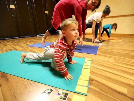 Klavitter, 3, holds a pose in toddler yoga at Body & Soul Wellness Center and Spa in Dubuque.