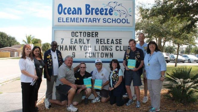 The Satellite Beach Lions Club donated 100 dictionaries with thesauruses to the third grade classes of Ocean Breeze Elementary last Wednesday. Pictured from left to right: Jacki Simpson, Assistant Prince Elizabeth Brodigan, Bill Mazyck, Curt Black, Alan Boleware, Ed Farnsworth, Gini Black, Joe Hauser, Frank Armitage, Principal Laurie Hering.