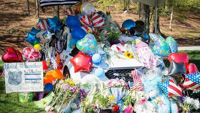 Flowers and balloons cover Officer Allen Jacobs' patrol car.