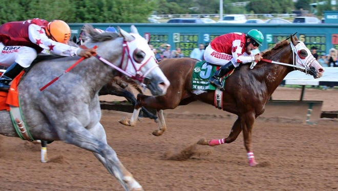 Imperial Eagle, outside, with Esgar Ramirez aboard, closes strongly to narrowly prevail over The Marfa Lights and jockey Larry Payne in the $3 million All American Futurity on Monday at Ruidoso Downs Race Track and Casino.