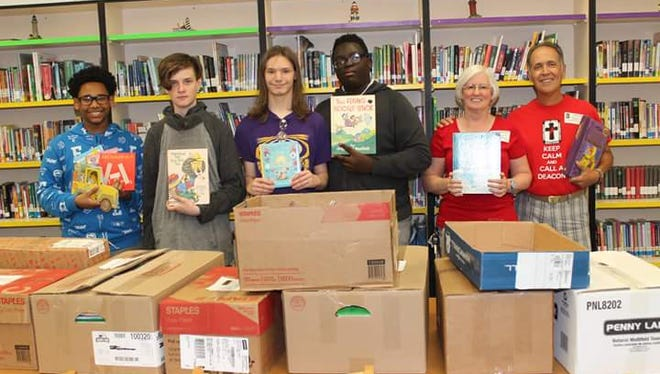 Northport students Marc Dorcin, Isaiah Evangelista, Nathan LeJeune and August Millang join Rad and Pat Orlandi as they unload 1005 books for NP summer reading program.