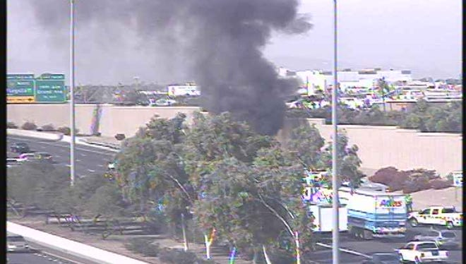 A smoke plume rises from a vehicle on fire on Interstate 10 westbound at the 19th Avenue exit on Nov. 20, 2017.