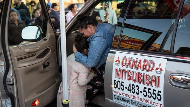 Maria Chagoya hugs her daughter while seated in the car she just won, a Lincoln Navigator refurbished by Oxnard students.
