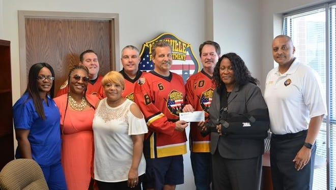 Members of the Nashville Fire Department Hockey Team, Seay Foundation, IAFF Local 140 President Mark Young and Director-Chief William Swann
