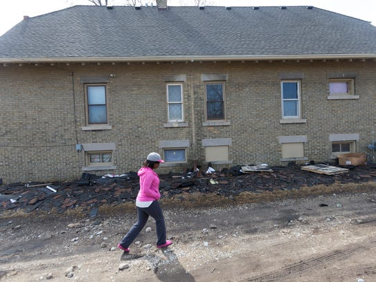 Destinie Grafton walks past old shingles outside the