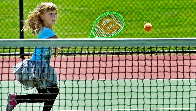 Lorelei McCurley, 5, gets tennis lessons from her dad, Scott McCurley, on Monday,  June 6, 2016 at Norlo Park, east of Chambersburg. Children are out of school for summer and occupying their time at area parks and in camps.
