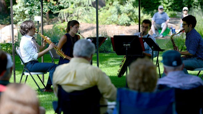 A saxophone quartet plays in 2016, in the Beal Botanical Garden at MSU as part of the Music in the Garden Concert Series through the College of Music.