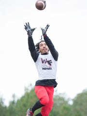 Amir McDaniel leaps for a ball during football practice