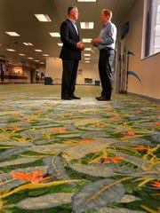 Greg Donovan, Orlando Melbourne International Airport executive director, and Roger Anderson Jr., BRPH director of design, stand atop the terminal's vintage bird of paradise carpeting near the domestic baggage claim.