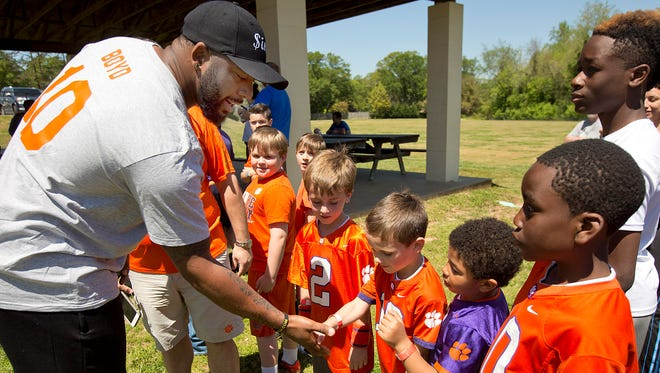 Tajh Boyd, left, and former Clemson teammate Sammy Watkins conducted a football camp for kids Sunday afternoon at the Caine Halter YMCA in Greenville. Tajh gets hand shakes and high-fives from young players.