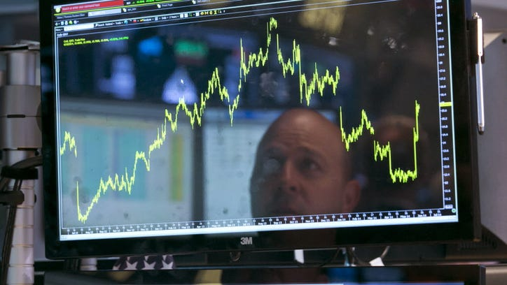 Specialist Jay Woods is reflected in one of the screens at his post on the floor of the New York Stock Exchange, Wednesday, June 18, 2014. U.S. stocks are little changed in early trading as investors wait for the latest policy action from the Federal Reserve. (AP Photo/Richard Drew) ORG XMIT: NYRD110