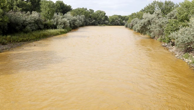 The discolored Animas River flows through Berg Park in Farmington on Aug. 8, 2015, shortly after the Gold King Mine spill.