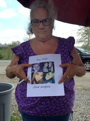Judy Manley holding a flyer with photos of her family