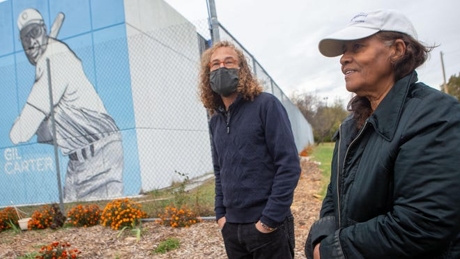 Artist Alexander Lancaster, left, listens Wednesday to Erma Forbes, right, president of the Gil Carter Initiative, 2450 S.E. 23rd St., describe the mural project featuring its namesake, Gil Carter.