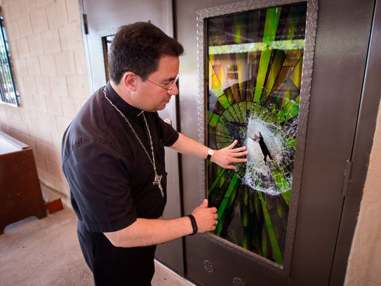Bishop Oscar Cantú examines broken stained glass at