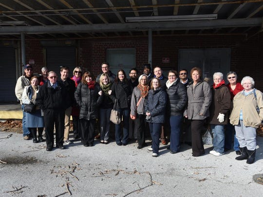 Current  and former Daily Times staff members pose in front of the newspapers' former building on Carroll Street.