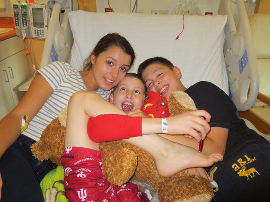 Jack (middle) gets a hug from siblings Ali (left) and Matthew at the hospital.