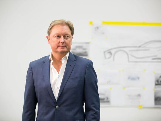 Henrik Fisker stands in front of a white board marked with drawing of an electric vehicle. His company announced this month that it is taking preorders for the EMotion vehicle.