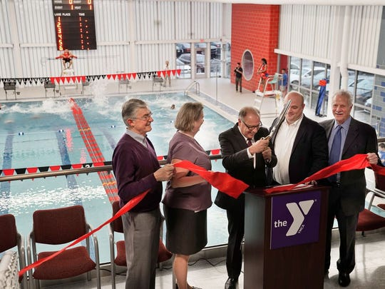 Mayor James Cassella, center, cuts the ribbon on the new aquatics center for the Meadowlands YMCA, as swimmers jump into the new pool behind him. Also pictured are Richard Branca of Branca Properties, YMCA President and CEO Jane Egan, board Chairman Ron Simoncini and Lloyd Rosenberg of DMR Architects.