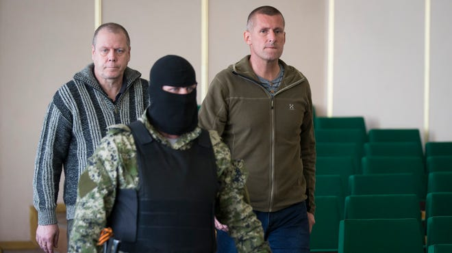 Two members of a group of foreign military observers are escorted by a pro-Russian militant to attend a news conference in the city hall of Slovyansk, eastern Ukraine, on Sunday.