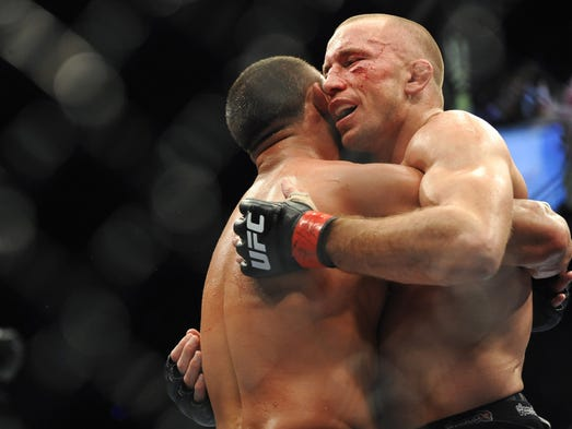 Georges St-Pierre (red gloves) and Johny Hendricks (blue gloves) hug after their welterweight championship bout during UFC 167 at MGM Grand Garden Arena.