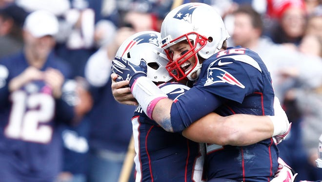 New England Patriots tight end Rob Gronkowski (87) and quarterback Tom Brady (12) celebrate a touchdown against the New York Jets during the second half at Gillette Stadium.