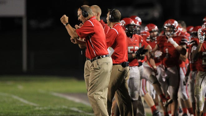 City High head coach Dan Sabers celebrates a fourth down conversion during the Little Hawks' game against Ottumwa at City High on Friday, Sept. 25, 2015.