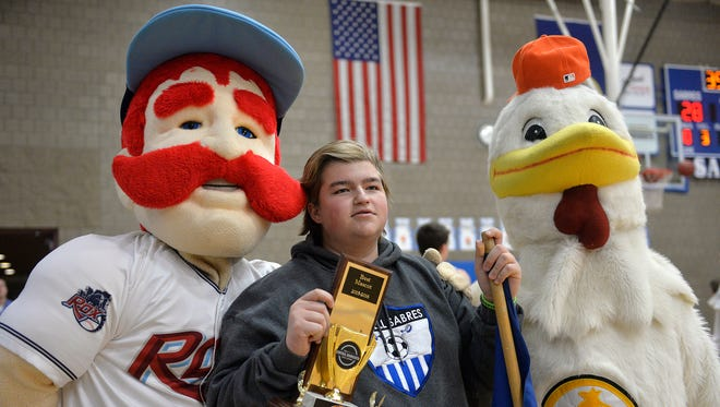 Sartell student body representative Trevor Erickson accepts the trophy for Central Minnesota's Best High School Mascot/nickname on Tuesday night. Also presenting the trophy were Chisel of the St. Cloud Rox and the Gold'n Plump Chicken from GNP. GNP is a sponsor of the online contest.
