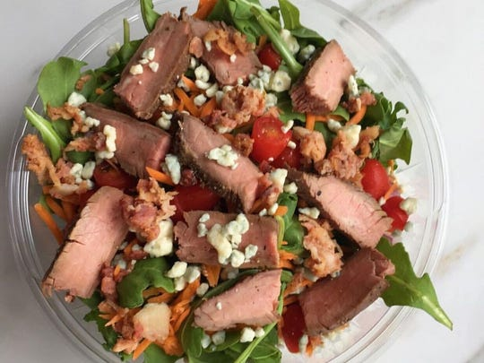 This Steakhouse Salad from Marie's Sandwich Bar features Angus flank steak with mixed greens, caramelized onions, Chimichurri ranch dressing and blistered cherry tomatoes.
