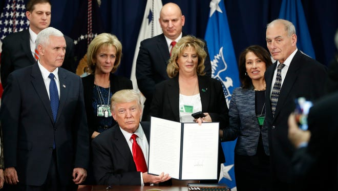 President Donald Trump holds up an executive order for immigration actions on Jan. 25, 2017, at the Department of Homeland Security in Washington, D.C.